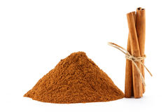 Cinnamon powder and sticks. Ground cinnamon powder and sticks on white isolated background Royalty Free Stock Photography