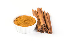 Cinnamon powder and cinnamon sticks. Isolated on white background Stock Photo