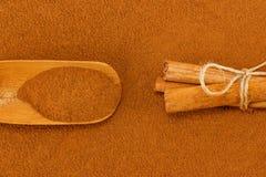 Cinnamon powder, sticks and scoop. Ground cinnamon powder and sticks, with bamboo gauge scoop royalty free stock images