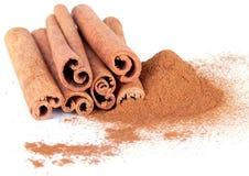 Cinnamon powder and sticks on white. Backhround Royalty Free Stock Photos