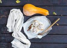 Cinnamon pumpkin buns with creamy cheese icing and ripe pumpkin Stock Photos