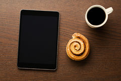 Cinnamon roll, cup of coffee and computer tablet Stock Photos