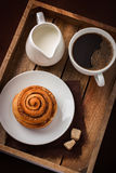 Cinnamon roll,  cup of coffee and cream  on wooden tray Stock Image