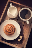 Cinnamon roll,  cup of coffee and cream  on wooden tray Royalty Free Stock Images