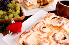 Cinnamon rolls. A plate of fresh baked cinnamon rolls with a bowl of grapes Stock Photo