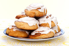 Cinnamon rolls. A plate of freshly baked cinnamon rolls with sweet, white icing dripping down the sides Stock Photos