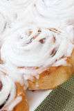 Cinnamon rolls. Hot out of the oven on a white plate and green place mat Stock Image