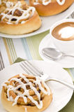 Cinnamon Rolls. Fresh hot cinnamon rolls straight from the oven with a coffee Stock Image