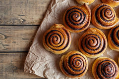 Cinnamon rolls buns christmas baking on a wooden breakfast table and parchment paper.Top view. Royalty Free Stock Photography