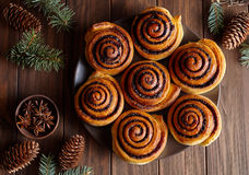 Cinnamon rolls buns christmas baking on a wooden breakfast table. Top view. Festive decoration with pine cones. And Christmas tree Royalty Free Stock Image