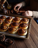 Cinnamon rolls buns with cocoa and spices on a metal baking sheet. Kanelbulle - swedish pastry dessert. Cinnamon rolls buns with cocoa and spices on a metal a Royalty Free Stock Photography