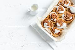 Cinnamon rolls. Or cinnabons with cream sauce, homemade recipe preparation sweet traditional dessert buns pastry food. Food ingridients for  on white table royalty free stock photography