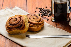 Cinnamon rolls with coffee beans on cloth napkin. With knife on wood table Stock Photos