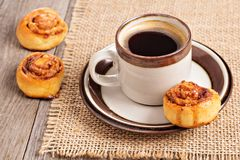Cinnamon rolls with coffee. In a brown cup Royalty Free Stock Images