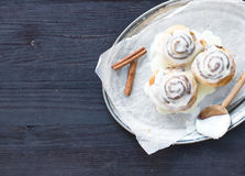 Cinnamon rolls with cream-cheese icing and cinnamon sticks on a Stock Photo