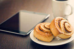 Cinnamon rolls, cup of coffee and computer tablet Stock Image