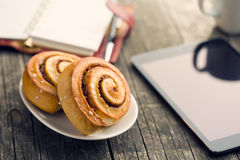 Cinnamon rolls, cup of coffee and computer tablet. Business breakfast Stock Photography
