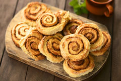 Cinnamon Rolls. Freshly prepared homemade cinnamon rolls on wooden board with tea in cup in the back (Selective Focus, Focus on the middle of the top cinnamon Royalty Free Stock Photos