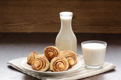 Cinnamon rolls with glass and bottle of milk Royalty Free Stock Photography