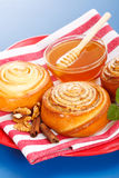 Cinnamon rolls and honey. Macro of cinnamon rolls and honey on red plate, blue background Stock Image