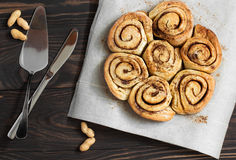 Cinnamon rolls and nuts on a wooden breakfast table. Buns with cinnamon on a wooden background, knife and blade Royalty Free Stock Photography
