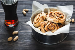 Cinnamon rolls and peanuts on the wooden background. Round buns with cinnamon and peanuts on the wooden background Royalty Free Stock Images