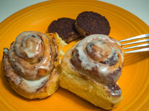 Cinnamon Rolls Sausahe Patties Plate. Orange plate of cinnamon rolls with two sausage patties and a fork royalty free stock photos