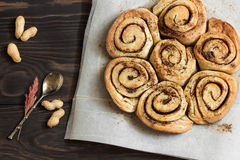 Cinnamon rolls  on a wooden breakfast table. Buns with cinnamon and nuts on a wooden background Royalty Free Stock Images