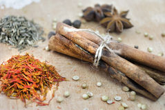 Cinnamon, safron, star anise and peper on a wooden table Royalty Free Stock Photography