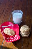 Cookies and milk on a mitten plate. Cinnamon snicker-doodle cookies and milk on a mitten plate  rest on a wood background Stock Photo