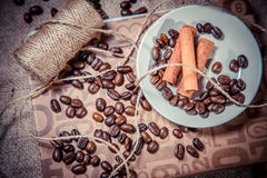 Cinnamon and spillage of coffee beans Stock Images