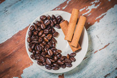 Cinnamon and spillage of coffee beans Royalty Free Stock Photos