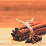 Cinnamon and star anise on a wooden background. Beautiful and fragrant spices for Christmas time and winter cooking season. Stock Images