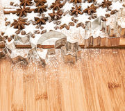 Cinnamon stars and cookies cutters on wooden background Stock Photos