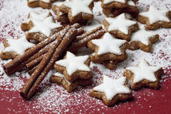 Cinnamon stars and spices sprinkled with powder sugar on red background Stock Image