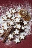 Cinnamon stars and spices sprinkled with powder sugar on red background Stock Images