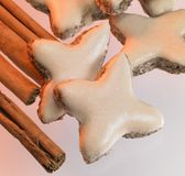 Cinnamon stars and sticks. Cinnamon-flavored christmas cookies and cinnamon sticks in light blurry back stock photo