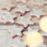 Cinnamon stars at wooden background stock image