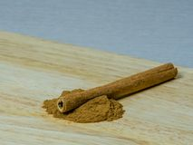 Cinnamon stick on cinnamon powder. Single cinnamon stick laying on cinnamon powder on a wooden cutting board Royalty Free Stock Photography