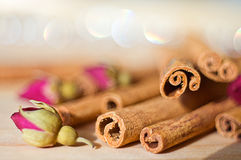 Cinnamon stick and rose buds. Cinnamon sticks and tea rose buds on a wooden table with some blur bokeh in the background. Take in August, 2010, in the USA, IL royalty free stock photo