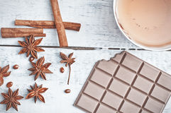 Cinnamon stick, star anise, bar of chocolate and cup of tea Royalty Free Stock Photos