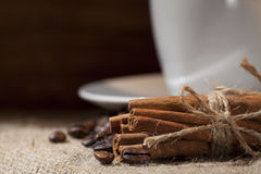 Cinnamon sticks. And coffee beans on a sack of coffee beans under stock photo