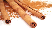 Cinnamon Sticks. Three cinnamon sticks and powder on a white background Royalty Free Stock Photo
