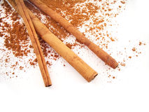 Cinnamon Sticks. Three cinnamon sticks and powder on a white background Royalty Free Stock Images
