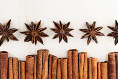 Cinnamon sticks and anise star closeup on white wood background. Royalty Free Stock Image