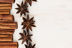 Cinnamon sticks and anise star closeup on white wood background. Royalty Free Stock Photo