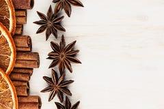 Cinnamon sticks, anise star and oranges closeup on white wood background. Stock Photos