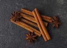 Cinnamon sticks and anise stars on a black stone background. Condiments on a dark table Stock Photos