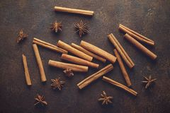 Cinnamon sticks and anise stars on the brown rusty backround. Stock Photos