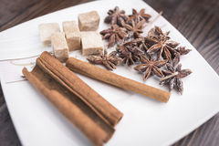 Cinnamon sticks, anise stars and pieces of brown sugar lie on a white square saucer. On a brown wooden background Stock Photos